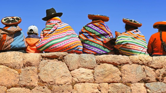 People sitting on a stone wall in colorful clothes or blankets and hats.
